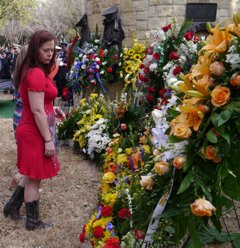 A mourner stops to look at flowers at the funeral services for Dallas firefighter William Scott Tanksley.