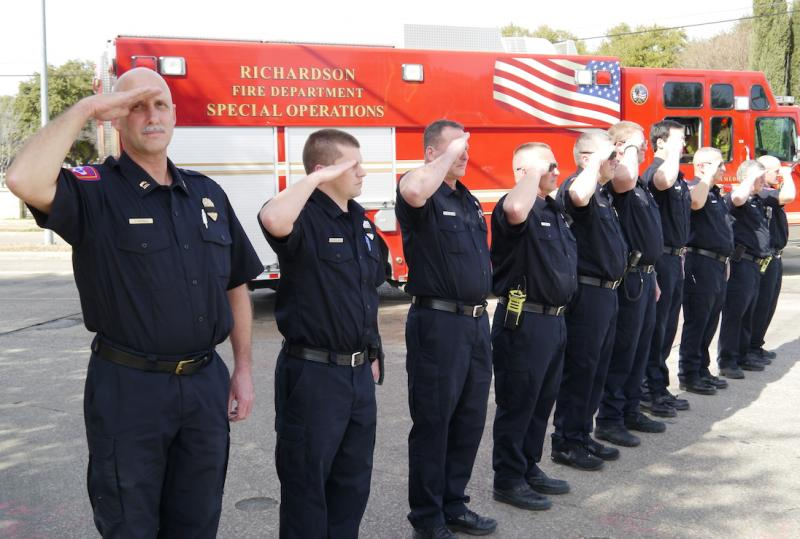 Rescue workers from the Richardson Fire Department salute as a procession of emergency vehicles travel toward Dallas' Restland Funeral Home.
