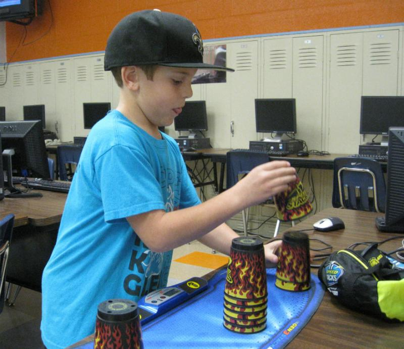 Nine-year-old Carson demonstrates his cup-stacking technique.