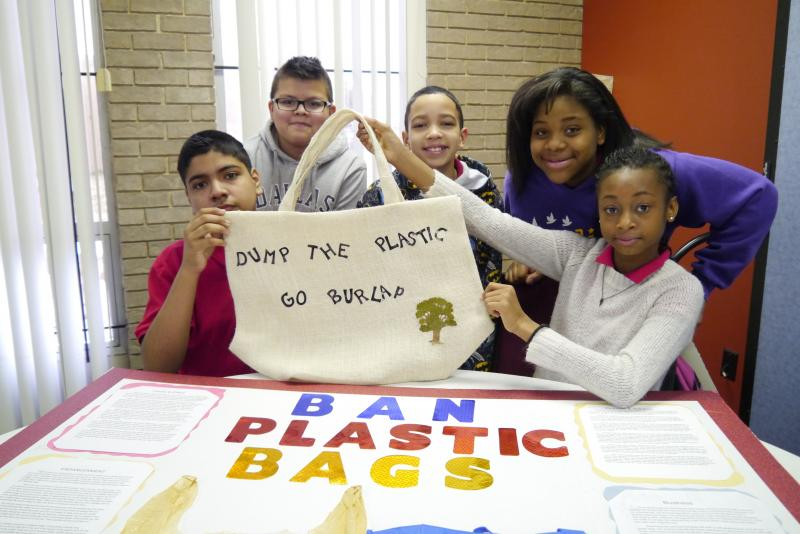 Student Camille Williams and classmates Legacy Prep School hold up a burlap bag as an alternative to a plastic bag.