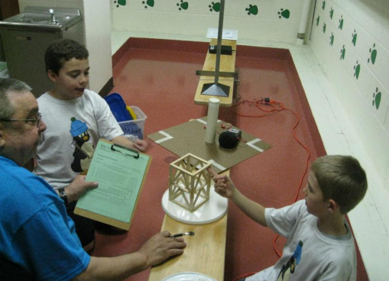 DI volunteer Doug Epperson (l) checks in the balsa structure from Kyle Barron (immediate rt of Epperson) and Kalder Korte