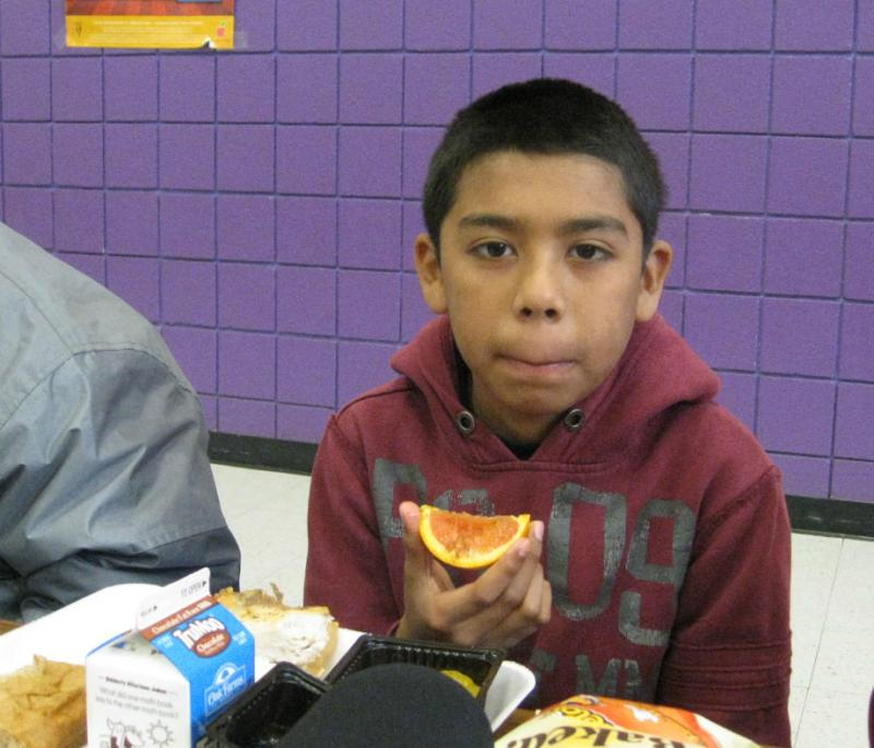 5th grader Eric Gonzalez samples a slice of juicy Cara Cara orange sprinkled with cinnamon