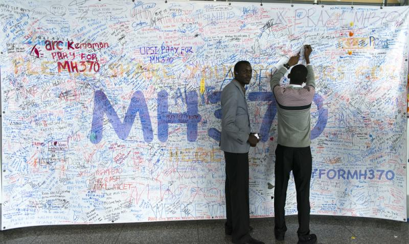 These two men were among many who wrote messages and prayers at Kuala Lumpur International Airport for Malaysia Airlines Flight 370.