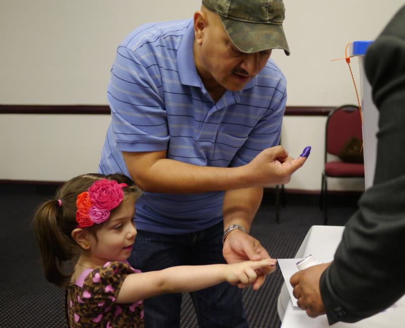 Masdi Altimimi shows his 4-year-old daughter how to vote in Dallas.