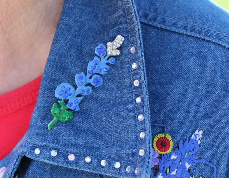 Sandy Anderson admits she's a bluebonnet addict. Here's her bluebonnet pin. She also has bluebonnet earrings, a bluebonnet bracelet and many bluebonnet shirts and jackets.