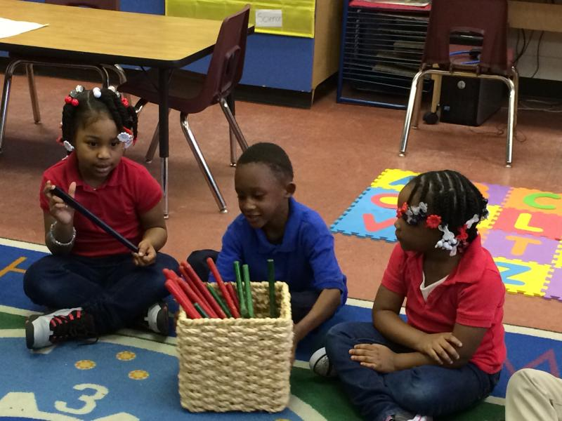 Pre-K students practice counting as they put away rhythm sticks.