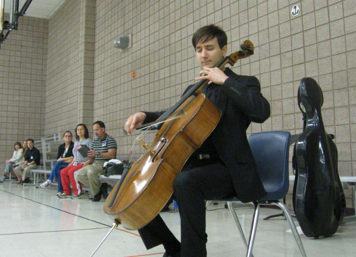 Dallas Chamber Symphony cellist Oliver Schlaffer plays Bach on his prized cello in front of Rutherford Elementary School students.