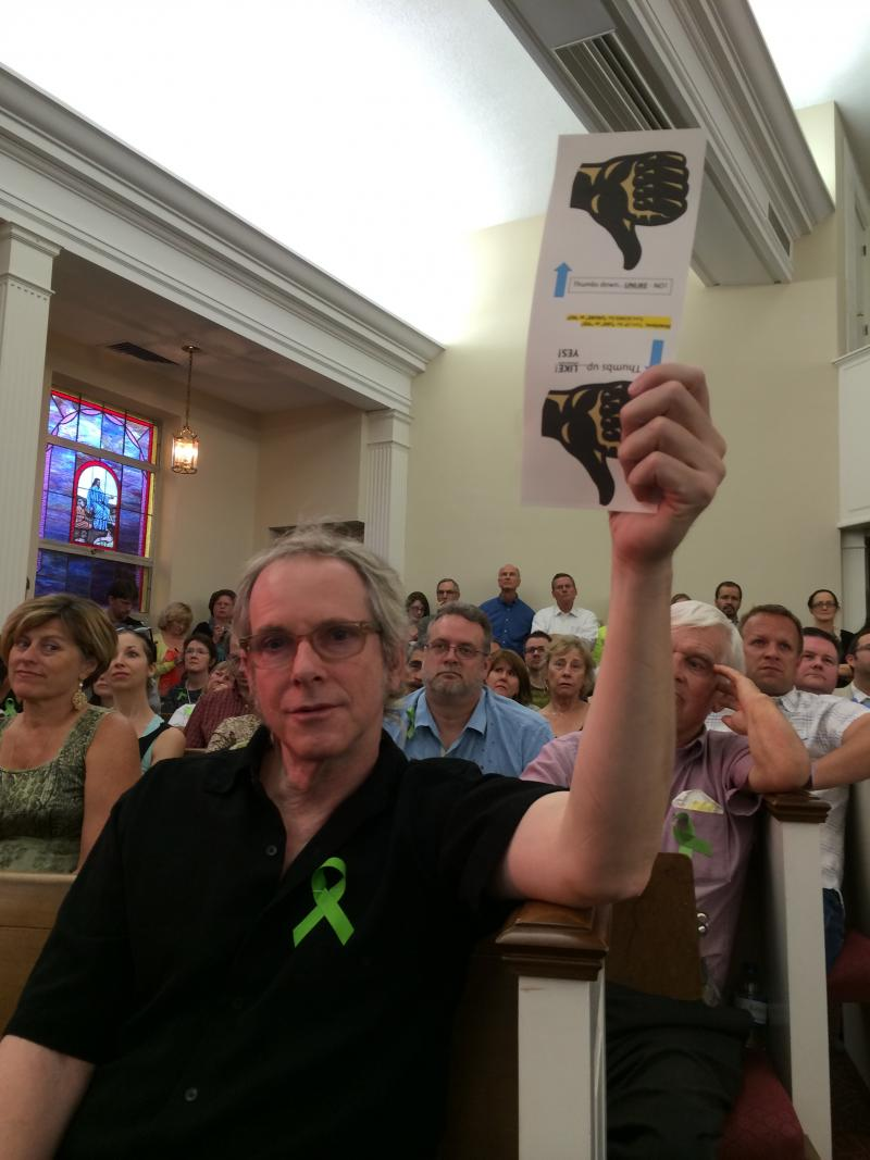 Opponents to a restaurant near White Rock Lake wore green ribbons and held up cards with a thumbs down image.