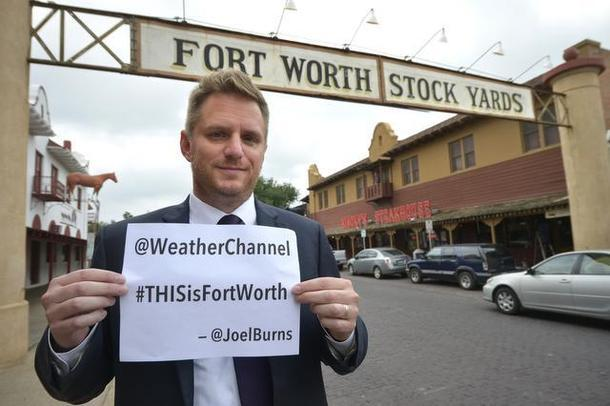 Fort Worth City Council member Joel Burns held a sign in the Stockyards Monday. His tweet to The Weather Channel ignited a social media storm.