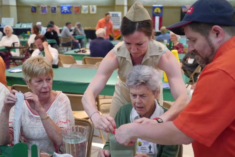 Ammie Rogers, who's father helped plan the Gainesville reunion, helps guests open a K-ration package, a new version of a meal in a bag that was used during World War II.