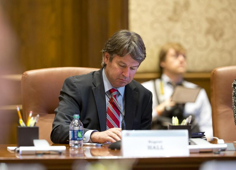 Dallas businessman Wallace Hall, Jr. took notes at a University of Texas Board of Regents meeting in 2013.