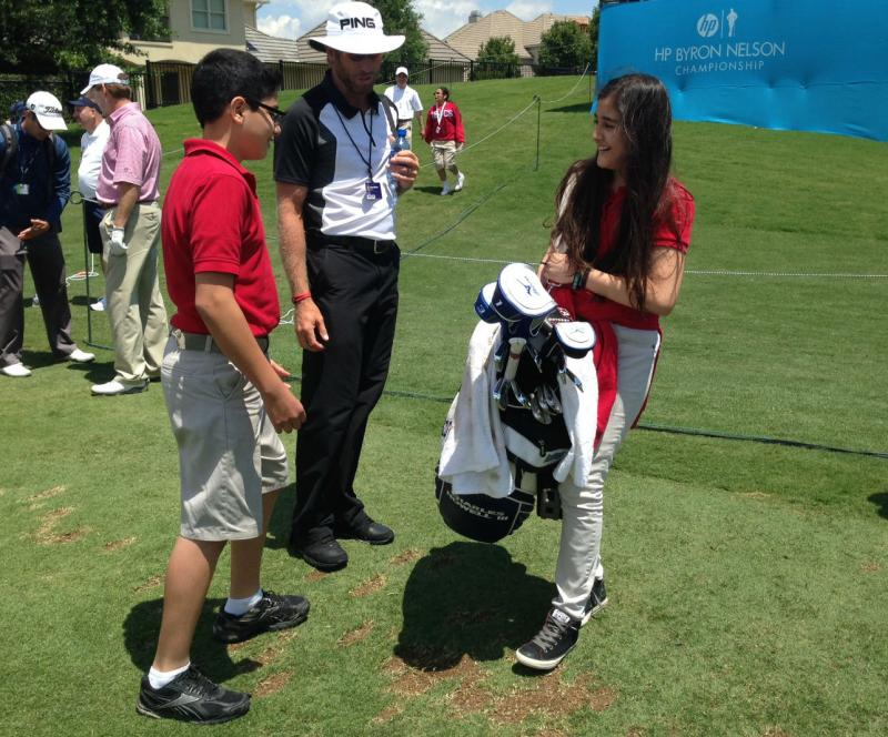 "Hedy Rojas, 11, tries carrying the golf bag belonging to professional player Charles Howell III. Rojas said it was ""really heavy."""
