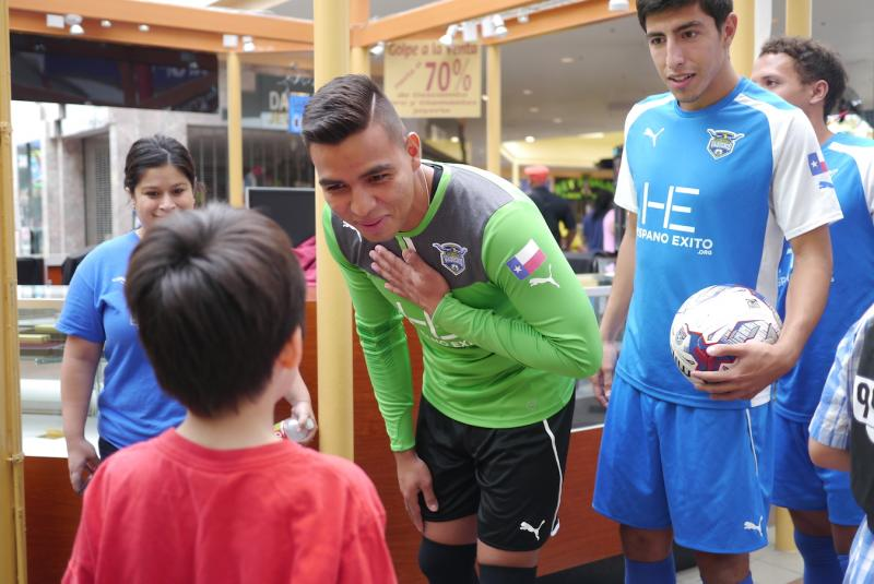 Arturo Sanchez, goalie for the Fort Worth Vaqueros, greets kids signing up for free backpacks at La Gran Plaza.