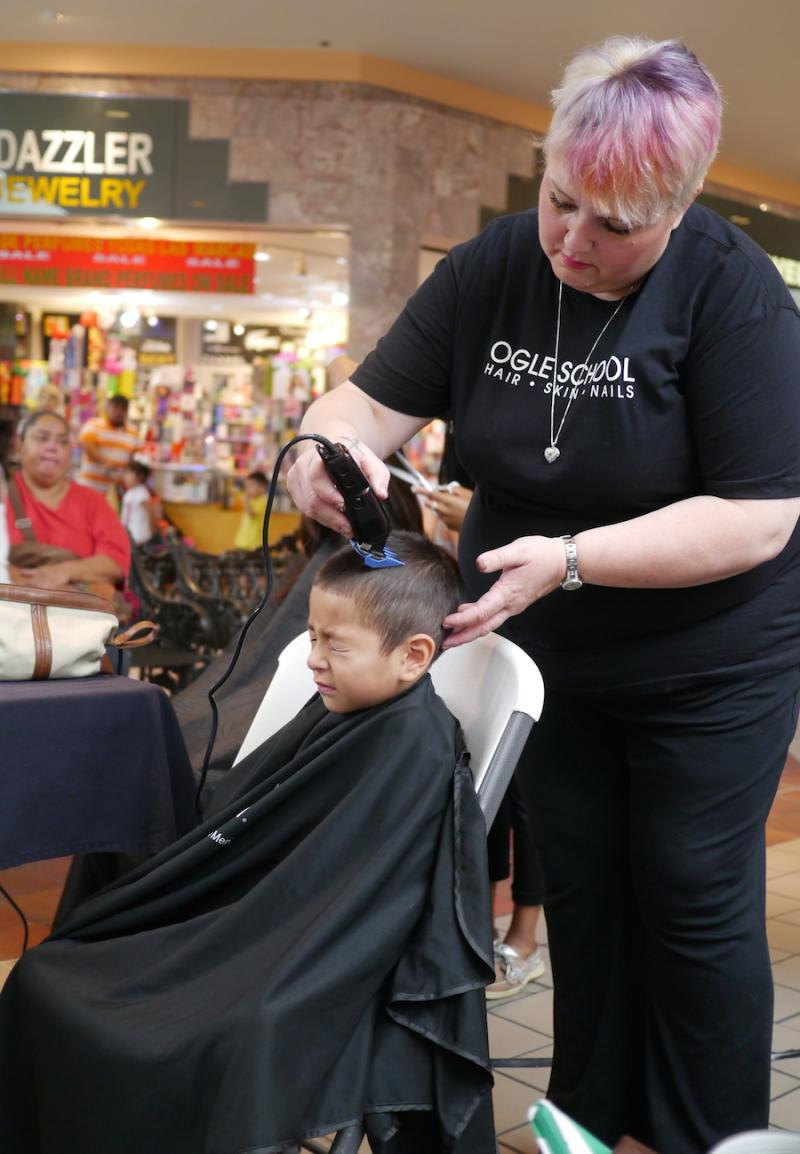 Stylists from the Ogle School of Texas give kids free haircuts at La Gran Plaza in Fort Worth.