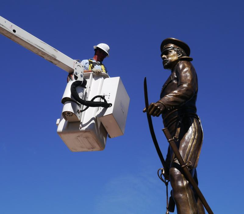 A worker helps to set the new bronze statue honoring the founder of Fort Worth, US Army Maj. Ripley Allen Arnold.