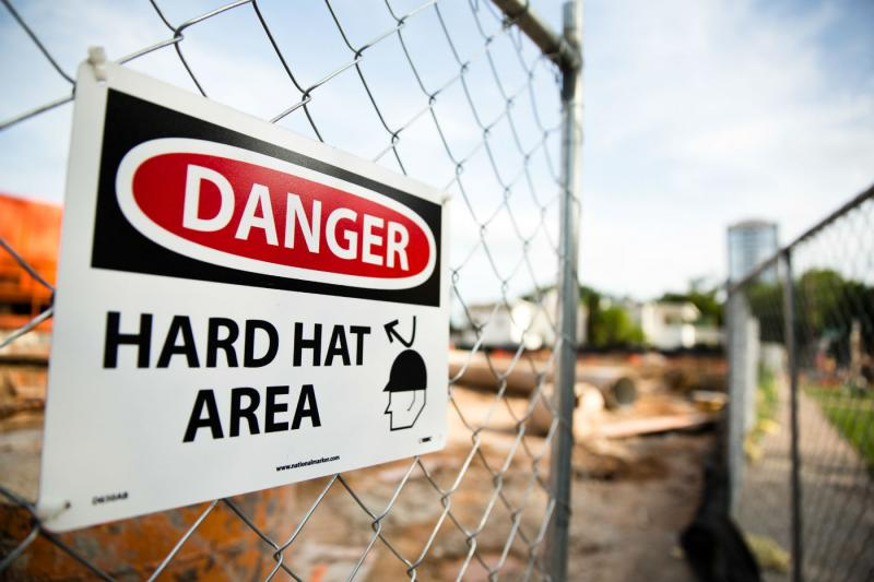 A sign at a construction area in Austin warns workers to wear protective gear.