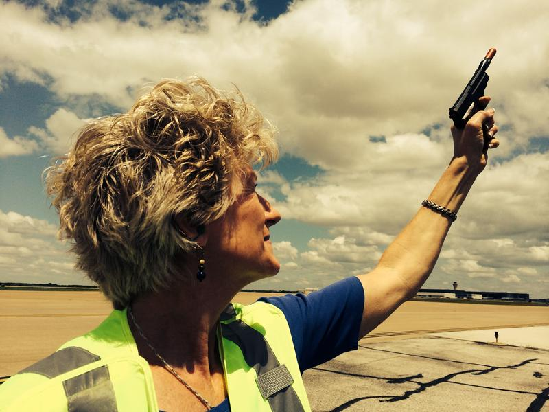 D/FW Wildlife Biologist Cathy Boyles fires sound cartridges from her pyrotechnic launcher to disperse birds that could damage planes at D/FW International Airport.