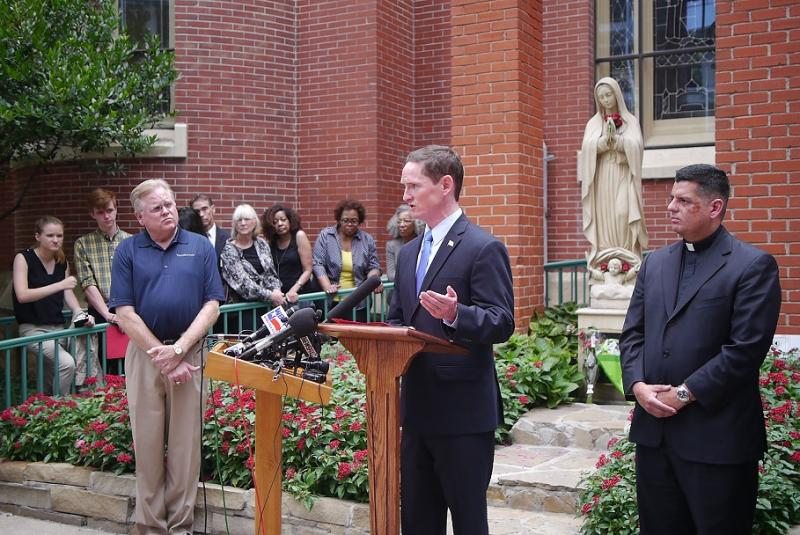 Dallas County Judge Clay Jenkins talks in front of the Cathedral Shrine of the Virgin Guadalupe.