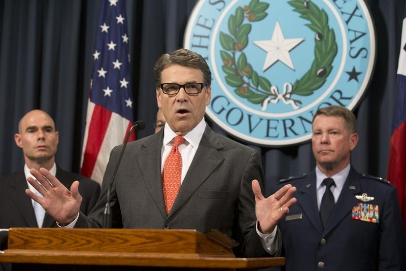 Gov. Rick Perry, flanked by State Rep. Dennis Bonnen (L) and Texas Adjutant General John Nichols (R), announced the deployment of National Guard troops to the Texas border on July 21.