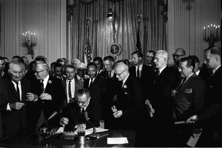 President Lyndon B. Johnson signed the 1964 Civil Rights Act as Martin Luther King, Jr., and others looked on.
