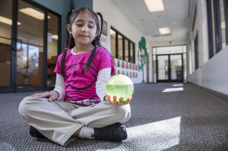 A student at Momentous Institute shows off a glitter ball. These balls help teach children how to cope with stress and anxiety.