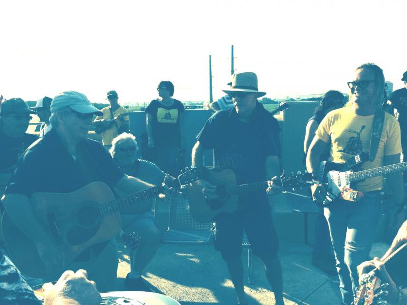 "Joe Dealcuaz, right, plays ""You Ain't Going Nowhere"" by Bob Dylan and The Band with fellow demonstrators on the Continental Avenue Bridge Park Friday."