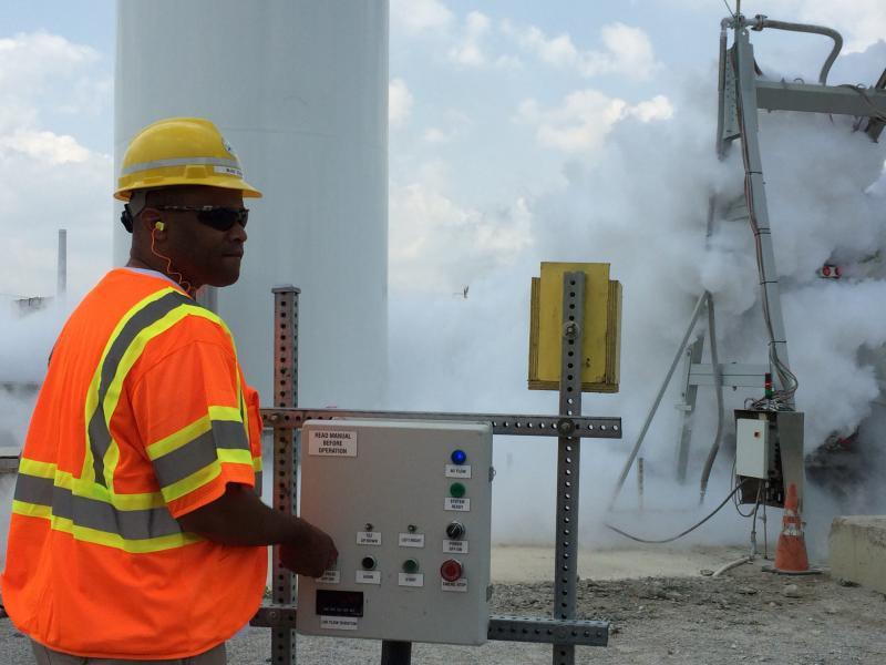 U.S. Rep. Marc Veasey operates controls that release liquid nitrogen into a cement mix.