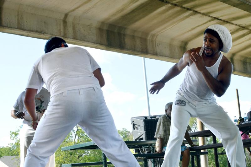 Two people perform capoeira, a Brazillian art form that combines acrobatics, martial arts and dance, in a pavillion to chanting and drum playing at Fair Oaks Park.