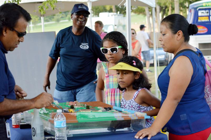 A family learns about water management at one of the dozens of booths at Turn Up! this past Saturday. Children can earn digital badges at each booth after finishing a learning activity. Badges can be used as a portfolio of the children's  accomplishments.