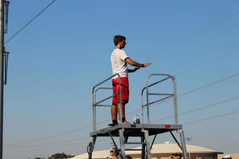 Senior drum major Bryan Dengler leads a section of the band from atop a tower.