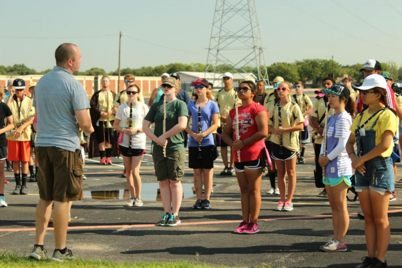 The Colony High School's associate band director Jason Brents gives instructions during the band's warm up.