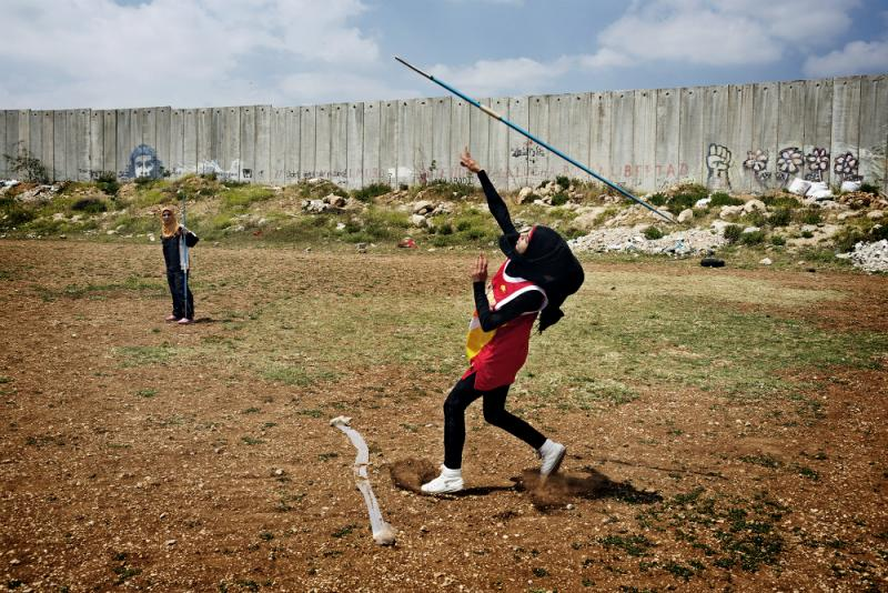 "From ""Occupied Pleasures"": Students from the Al-Quds University javelin team wrap up their last practice before summer vacation in the West Bank city of Abu Dis, next to the Israeli Separation Wall."