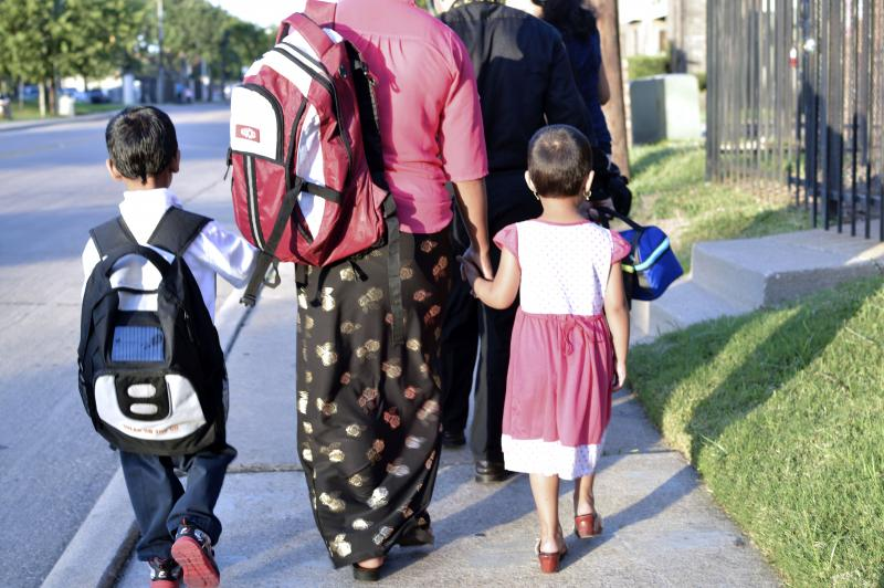 Tee Da Mo walks with her daughter and two sons to school. They arrived from Burma as refugees a few months ago.