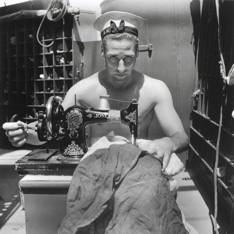 A Royal Navy sailor on board the HMS Alcantara uses a portable sewing machine to repair a signal flag during a voyage to Sierra Leone, dated March 1942.