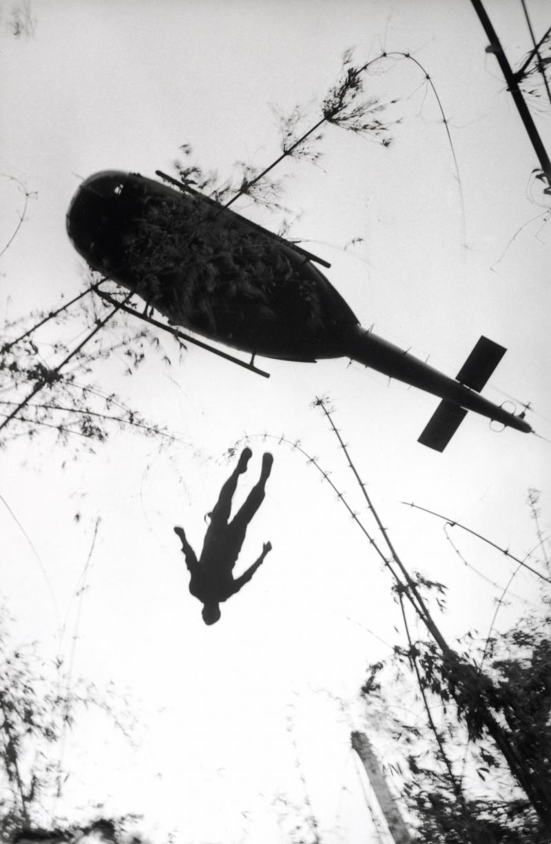 The body of an American paratrooper killed in action in the jungle near the Cambodian border is raised up to an evacuation helicopter in Vietnam, dated 1966.