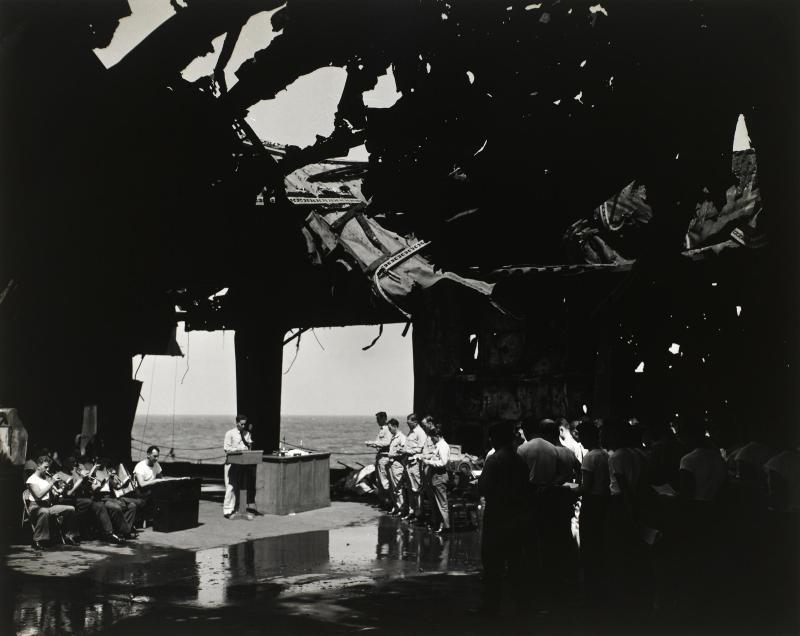 R. Woodward of the United States Navy Reserve took this photo of religious services under the blasted flight deck of the USS Franklin.