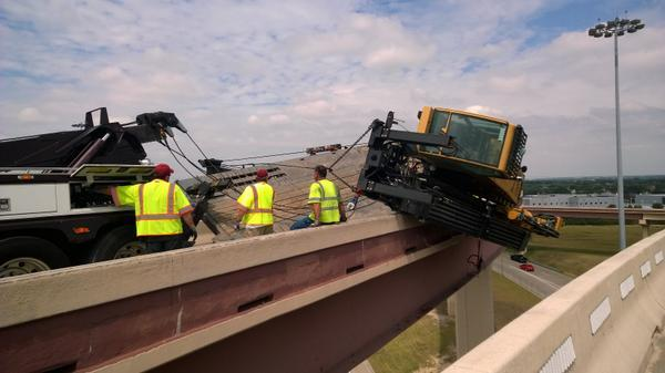 A crane has tipped over and is hanging over a bridge at President George Bush Turnpike and the Dallas North Tollway.