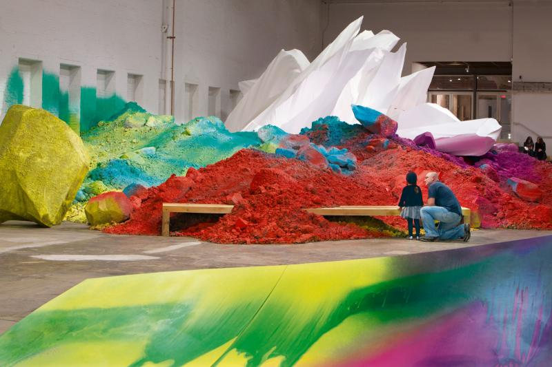 Katharina Grosse's installation of 'One Floor Up More Highly' combines sculptures made of dirt and wood with bright spray paint to create a sprawling and spectacular environment.