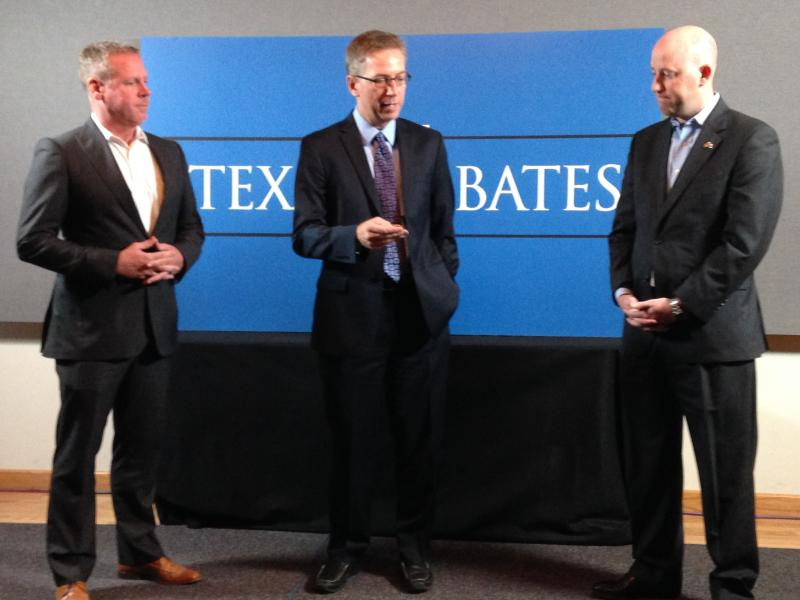 Tom Stewart with the Wendy Davis campaign (L) and Robert Allen with Greg Abbott's campaign (R) meet for the debate coin toss. KERA's vice president of news, Rick Holter, makes the flip.