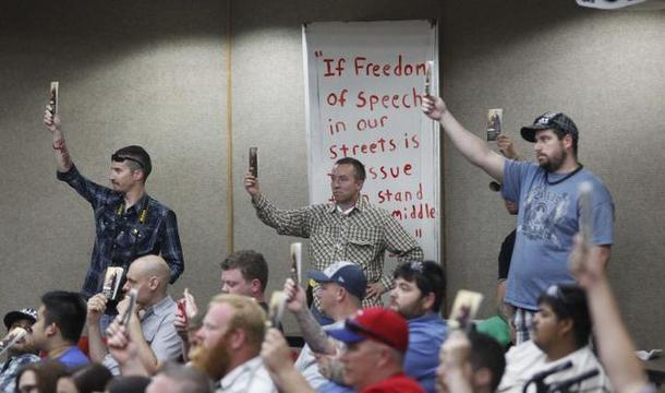 Members of Open Carry Tarrant County hold up copies of the U.S. Constitution during a discussion on the ordinance at the Arlington City Council meeting April 22.