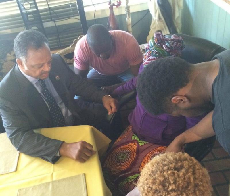 The Rev. Jesse Jackson Sr. prays with Ebola patient Thomas Duncan's family.