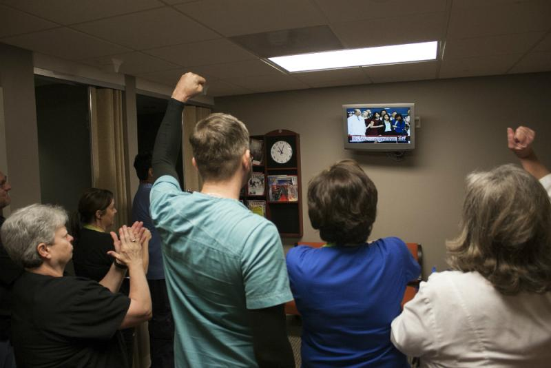 Emergency room nurses at Texas Health Presbyterian Hospital watch and cheer as Nina Pham gives her statement on television.