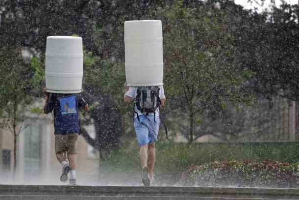 Two TCU students grabbed plastic barrels to shield them from the rain. A sudden, fierce and short storm blew in to Fort Worth yesterday afternoon with heavy rain and hail.