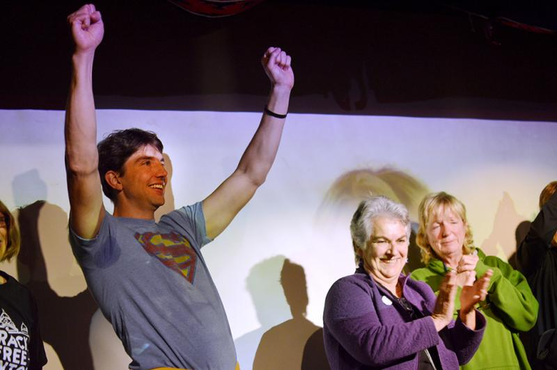 Adam Briggle, vice president of Frack Free Denton, throws up his arms after giving a victory speech to the watch party at Dan's Silver Leaf.
