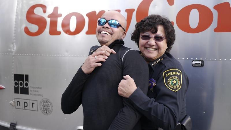 Dallas County Sheriff Lupe Valdez fools around with her dance partner before going inside StoryCorps MobileBooth.