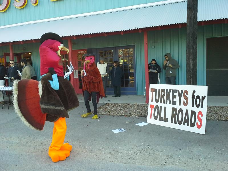 Protesters in seasonal dress call the proposed Trinity toll road a turkey of a project. They were stationed outside the mayor's announcement that a team of outside engineers and urban planners would re-imagine the design of the proposed Trinity Parkway.