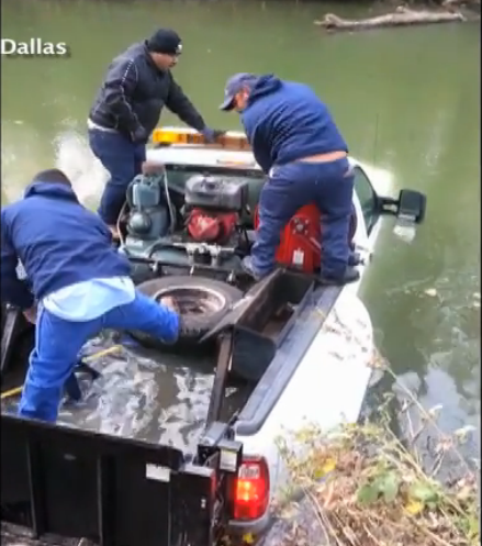 A picture from a YouTube video shows Dallas city workers rescuing an employee from a truck submerged in a creek.