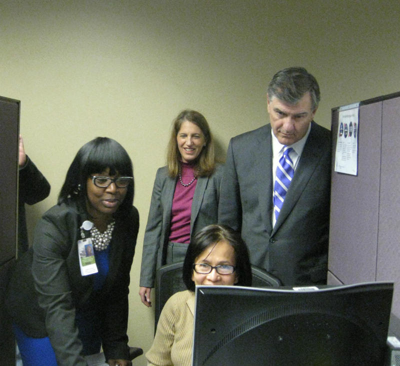 Health and Human Services Secretary Sylvia Burwell (center) stands behind Dallas Mayor Mike Rawlings as a health care assistant at Parkland helps the seated enrollee sign up for insurance
