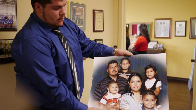 Jose Velasquez holds a family photo. He is a relative of one of the workers who died in last week's Downtown Dallas fire.