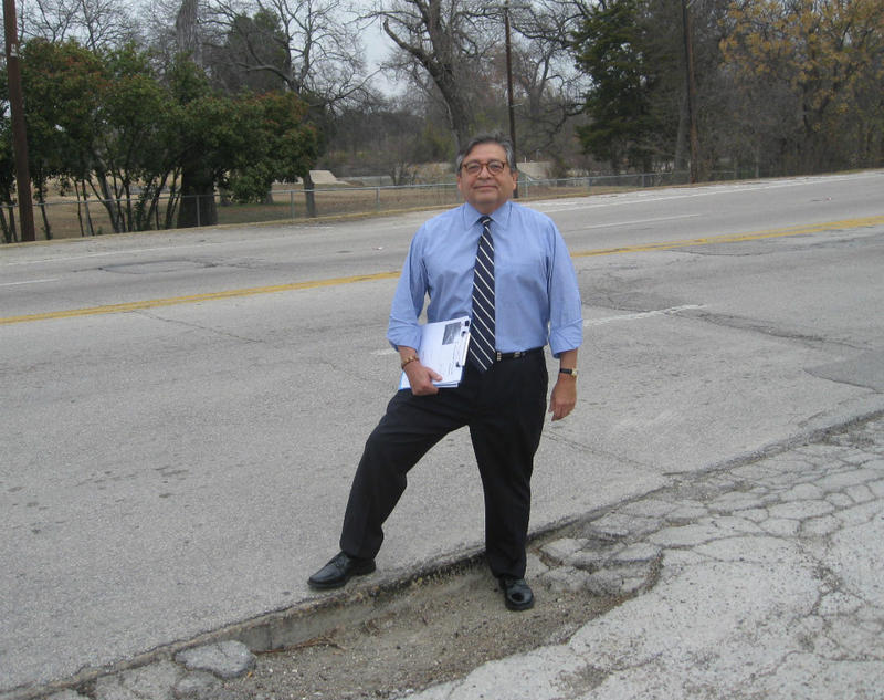 Marcos Ronquillo stands on a pot hole on Samuell Blvd to make his point that Dallas infrastructure needs more attention than it's getting now